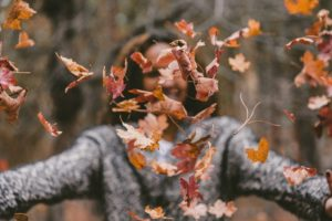 Woman throwing leaves to practice mindfulness in Dialectical Behavior Therapy Skills