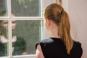 Teen girl staring out a window thinking about bulimia