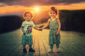 Two Children holding hands on a brick path
