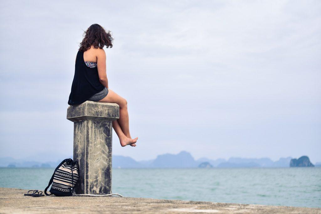 Person sitting on a stone pillar