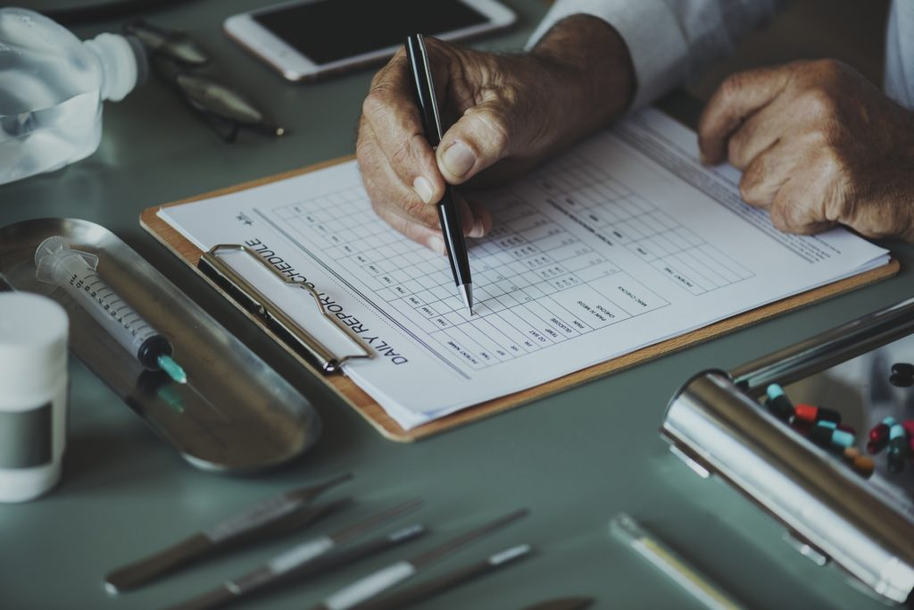 Doctor filling out form for medication-assisted treatments for depression