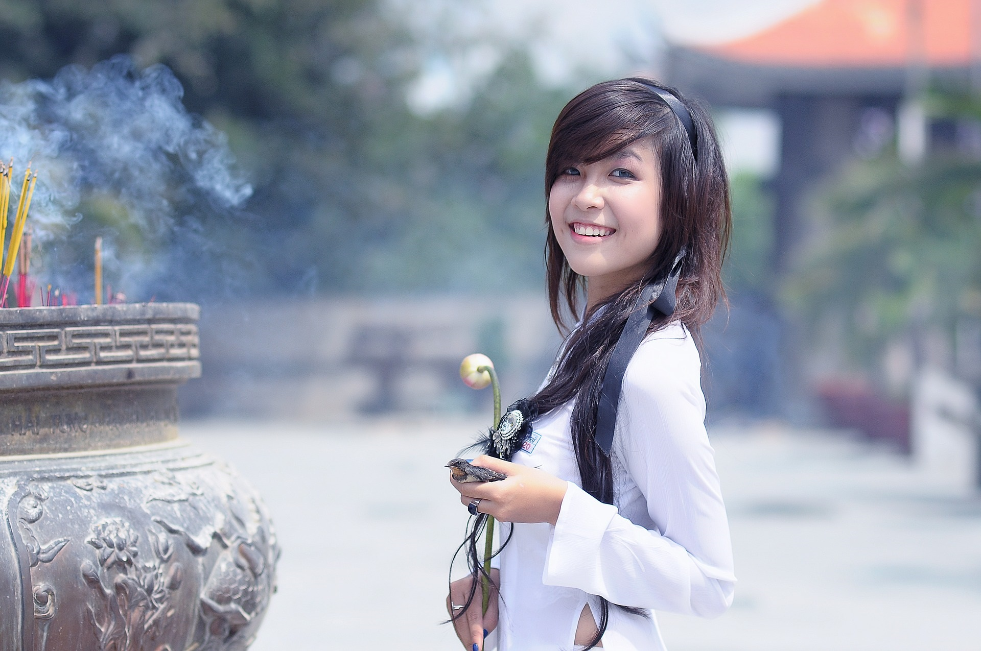 Asian American woman holding a flower