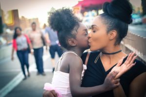 African-American lady kissing her daughter after overcoming summer eating disorder triggers