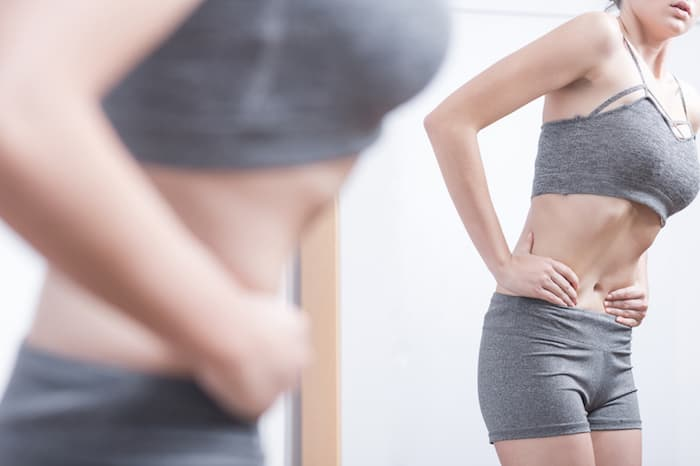 Female Looking at Her Body in a Mirror