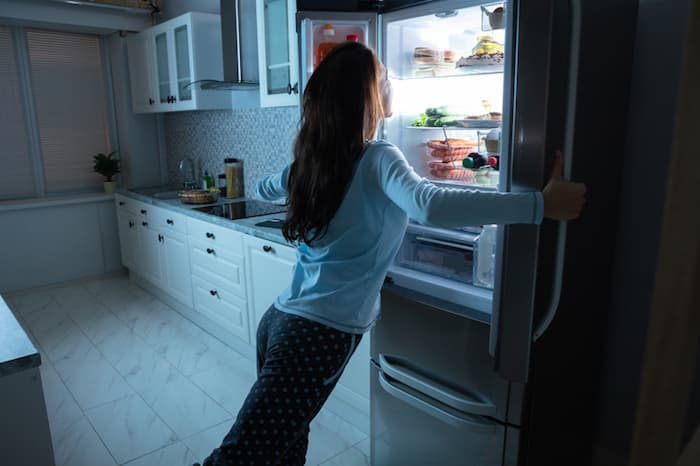 woman looking in refrigerator at night